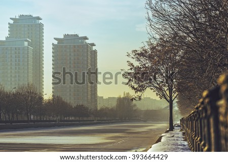 Morning cityscape with modern high rise block of flats on the bank of the frozen Dambovita river, in south-eastern Bucharest capital, Romania. Shallow depth of field. - stock photo