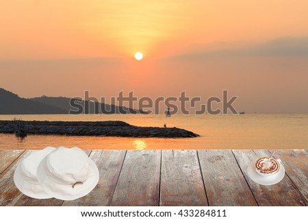 Morning coffee and White hat Two overlapping  on wood table at sunset or sunrise sea, The delicious aroma Cappuccino coffee : space for text  and may be used as background : - stock photo