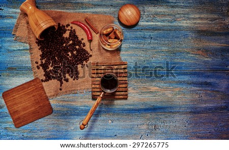 Morning coffee break served on the home kitchen of a country house, a crunchy biscuit in the bank next randomly scattered grains of coffee in a Cezve fresh brewed coffee  - stock photo