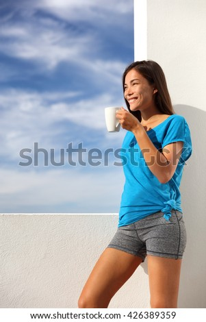 Morning coffee breakfast yoga woman in activewear at home outdoor terrace living. Asian fitness fit girl drinking enjoying summer sun outside after exercise workout. Healthy active lifestyle. - stock photo