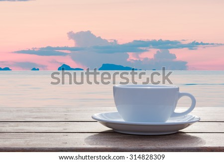 Morning coffee cup with beautiful sea  sky and puffy clouds background - stock photo