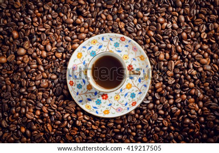 Morning coffee cup with saucer on background with coffee beans, top view.  - stock photo