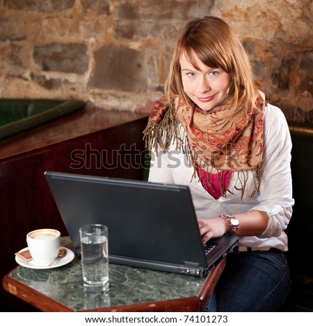 Morning coffee in internet cafe - Beautiful young girl checking news on web and drinking coffe - stock photo