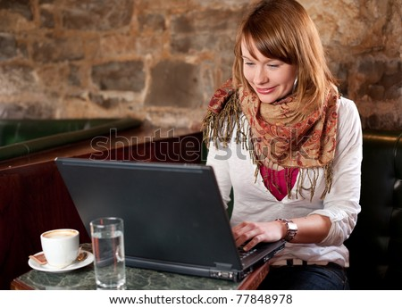Morning coffee in internet cafe - Beautiful young girl checking news on web and drinking coffee - stock photo