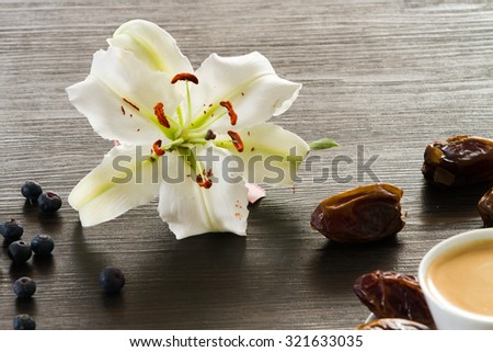 Morning coffee setting with dry dates, orange marmelade and white lily - stock photo