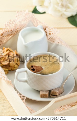 Morning coffee with cinnamon, milk, sugar and cookies on the white wooden table - stock photo