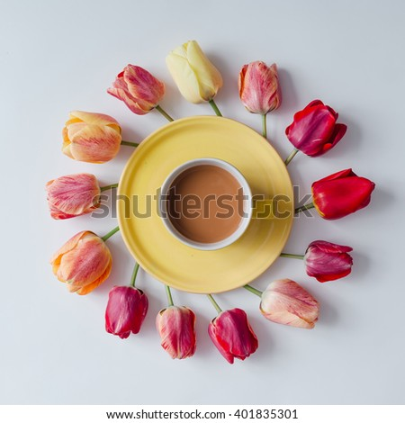 Morning coffee with creative arrangement of tulip flowers on bright background. Flat lay. - stock photo