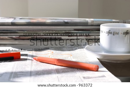 morning coffee with fresh newspapers (in search for the job) - stock photo