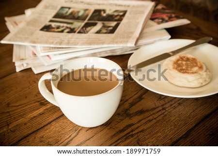 Morning coffee with newspaper and english muffin behind - stock photo