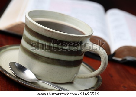 Morning coffee with the Bible in background. Shallow dof - stock photo