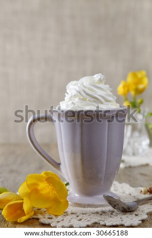 morning coffee with whipped cream, and fresia yellow flowers, shallow DOF - stock photo