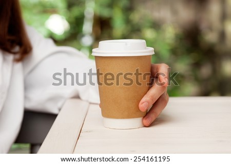 Morning coffee. Woman holds a disposable coffee cup - stock photo