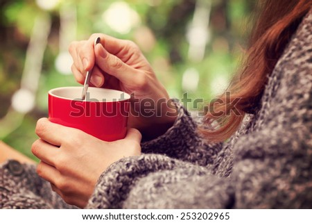 Morning coffee. Woman holds a red coffee cup - stock photo