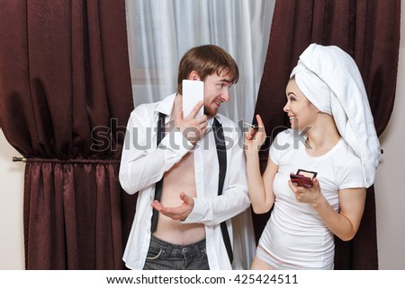 Morning couples. Husband and wife are going to work. Man talking on the phone. Girl doing make-up with a towel on her head. They talk to each other. - stock photo