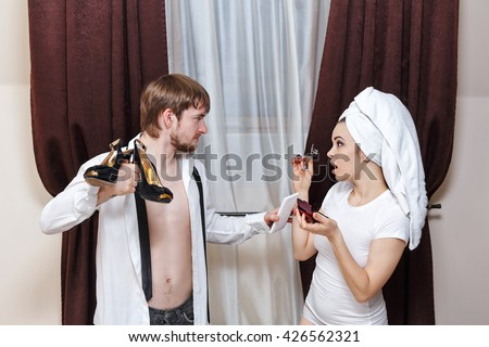 Morning couples. Husband and wife are going to work. The man brought her shoes. Girl doing make-up with a towel on her head. - stock photo