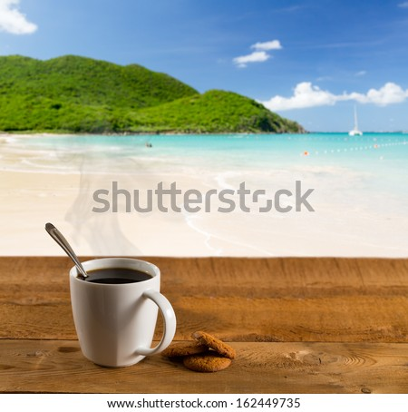 Morning cup of coffee on a wooden picnic table on Anse Marcel beach on St Martin in Caribbean in idyllic dreamlike location - stock photo