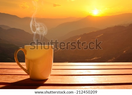 Morning cup of coffee with mountain background at sunrise - stock photo