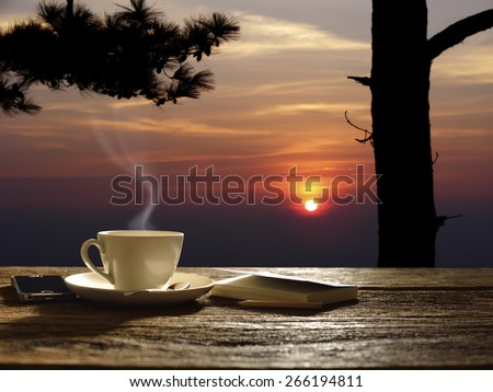 Morning cup of coffee with sunrise background - stock photo