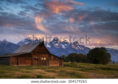 Morning drama in the sky above one of the Mormon Row barns in Wyoming's Grand Teton National Park. - stock photo