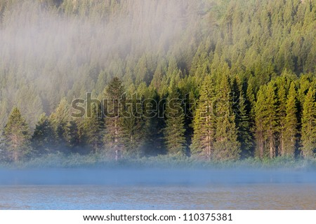 Morning fog at Swiftcurrent Lake as viewed from the Many Glacier Hotel in Glacier National Park, Montana - stock photo