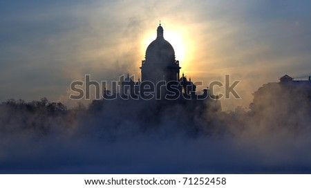 Morning fog during strong frosts on quay of the river of Neva and St. Isaac's Cathedral in Saint-Petersburg on the sky background. - stock photo