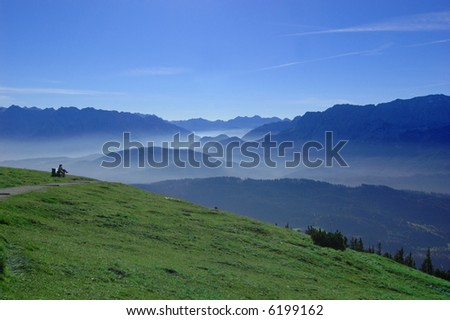 Morning fog in the mountains, 2 people on a bench in the distance enjoying the view - stock photo