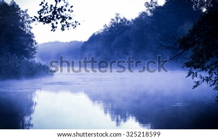 Morning fog on a calm river, tranquil scene on Seversky Donets river, Ukraine, cold color toned image - stock photo