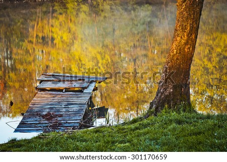 Morning fog over a pond, fishing bridge, trees and leaves reflected in the water - stock photo