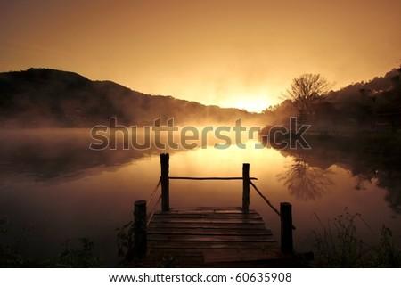 Morning fog over scenery lake at urban village, Mae Hong Son, Northern Thailand - stock photo