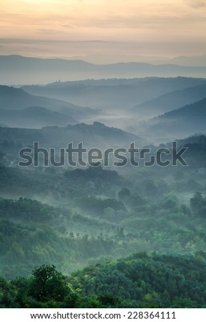 Morning fog over the valley in Tuscany - stock photo