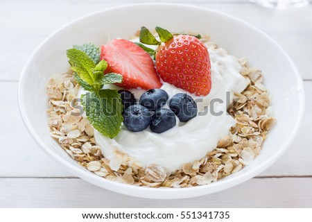 Morning healthy breakfast with muesli and berries on the white background. Top view