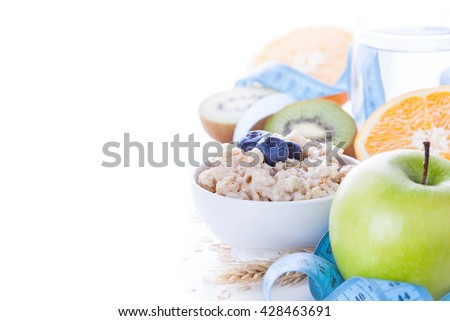 Morning healthy nutrition, diet frame with oatmeal porridge, fruits, mineral water and measuring tape. Perfect breakfast before workout