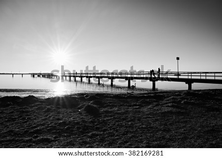Morning in harbor. Tourists walk on pier construction above sea. Sunny clear blue sky, smooth water level. Black and white photo - stock photo