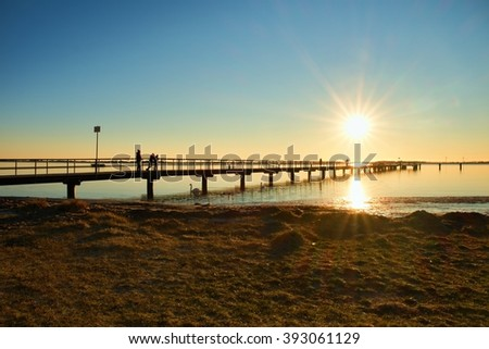 Morning in harbor. Tourists walk on pier construction above sea. Sunny clear blue sky, smooth water level - stock photo