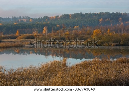 Morning lake at autumn. Beautiful landscape of wild misty lake at sunrise. Polish landscape