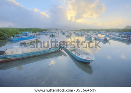 Morning landscape of Tamsui river with stranded boats during a low tide under moody sky, Taipei Taiwan ~ Scenery of beautiful sunrise by Tamsui river, Taipei Taiwan - stock photo
