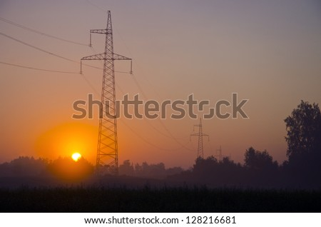 morning landscape with electricity transmission towers and sunrise - stock photo