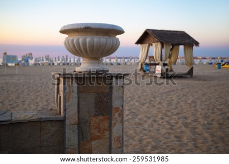 Morning landscape with plaster vase and a canopy on the sandy beach. Shallow depth of field. Focus on the old plaster vase. - stock photo