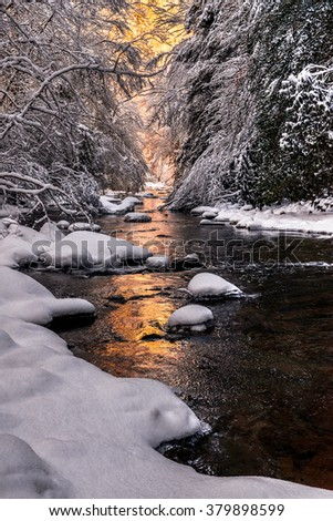 Morning light and fresh snow on Martins Fork of the Cumberland River in the Appalachian Mountains of Kentucky. - stock photo