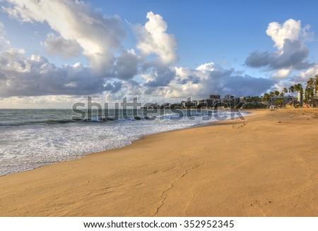 Morning light bathes tan-colored sandy beach in Maceio, Alagoas, Brazil - stock photo