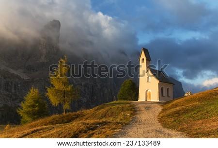 Morning light illuminated church in Passo Gardena and the Dolomites - stock photo