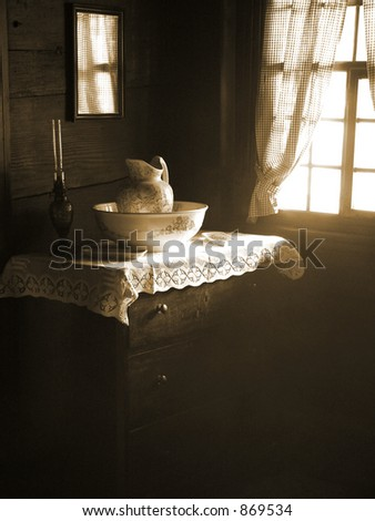 Morning Light illuminates a vintage scene with an old dresser and antique pitcher and wash basin. - stock photo