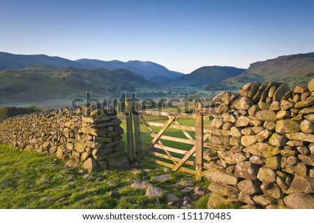 Morning light illuminating traditional dry stone wall, farmers gate in the  Lake District, Cumbria. - stock photo
