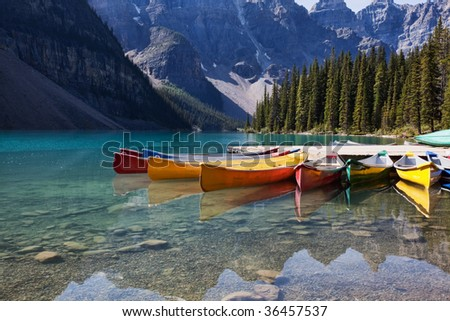 Morning light on colorful canoes along the shore of Moraine Lake, Banff National Park, Alberta, Canada. - stock photo