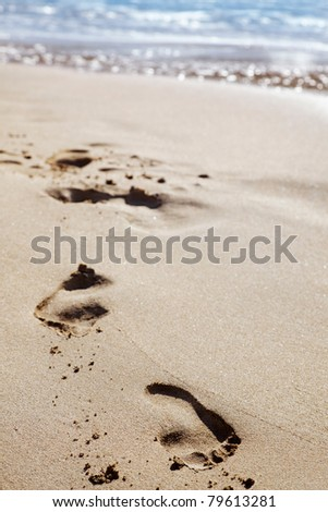 Morning light on footprints in the sand - stock photo