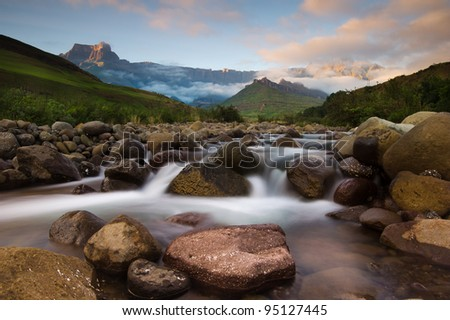 Morning light paints the peaks of the Drakensberg Mountains, with the Tugela river flowing gently below - stock photo