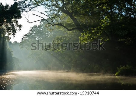 Morning light rays and fog on river. - stock photo