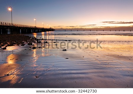 Morning light reflections from the jetty on the wet sand - stock photo