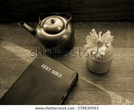 Morning Light Shines Across The King James Bible. Morning light illuminates a bible with a copper teapot and fresh flower. Shot from above with with a desaturated vintage filter applied. - stock photo