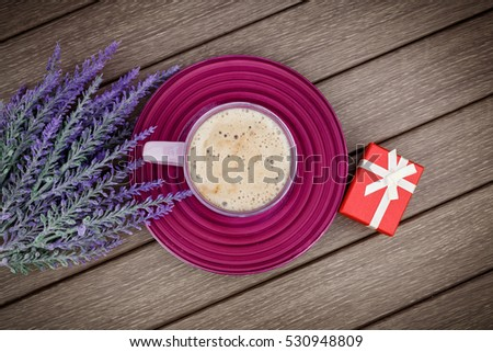 Morning lilac gift, cappuccino and flowers on wooden table